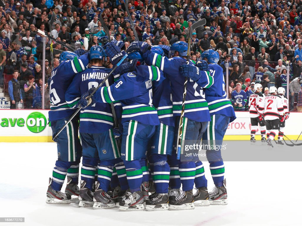 The Vancouver Canucks celebrate an overtime victory against the New Jersey Devils in their NHL game at Rogers Arena on October 8, 2013 in Vancouver, British Columbia, Canada. Vancouver won 3-2.