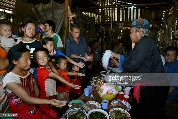 The Vang family go through a ritual as a shaman hands them strings to tie on their wrists during a 'good luck' ceremony before leaving for the US...