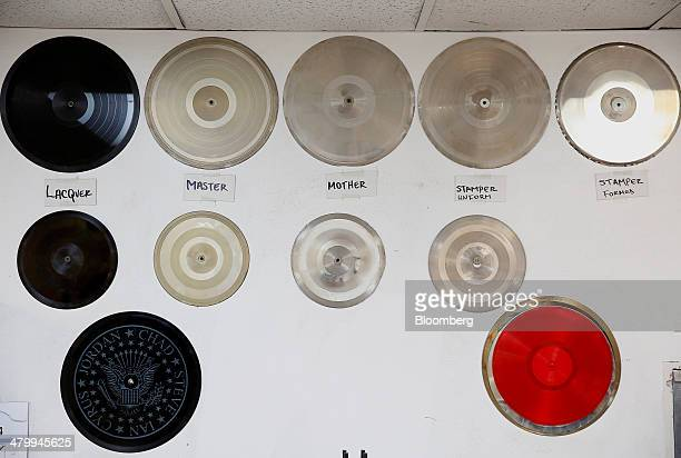 The various stages of how a vinyl record is made from the master mother and stamper are seen on a wall at the Rainbo Records manufacturing facility...