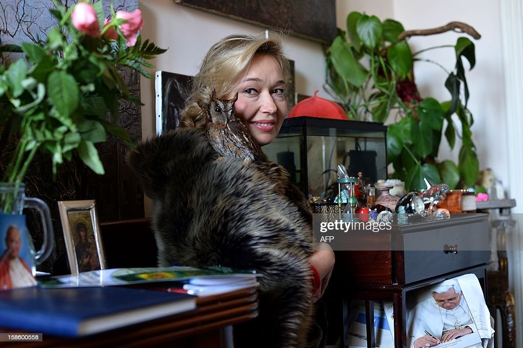 The Vatican's newest official court artist Natalia Tsarkova poses with her pet owl on December 18, 2012 in her studio by Rome. After Michelangelo and Raphael, the Vatican's newest official court artist is something of an unusual choice -- an ebullient Russian woman with a pet owl who meets cardinals and popes on a daily basis. AFP PHOTO / ALBERTO PIZZOLI