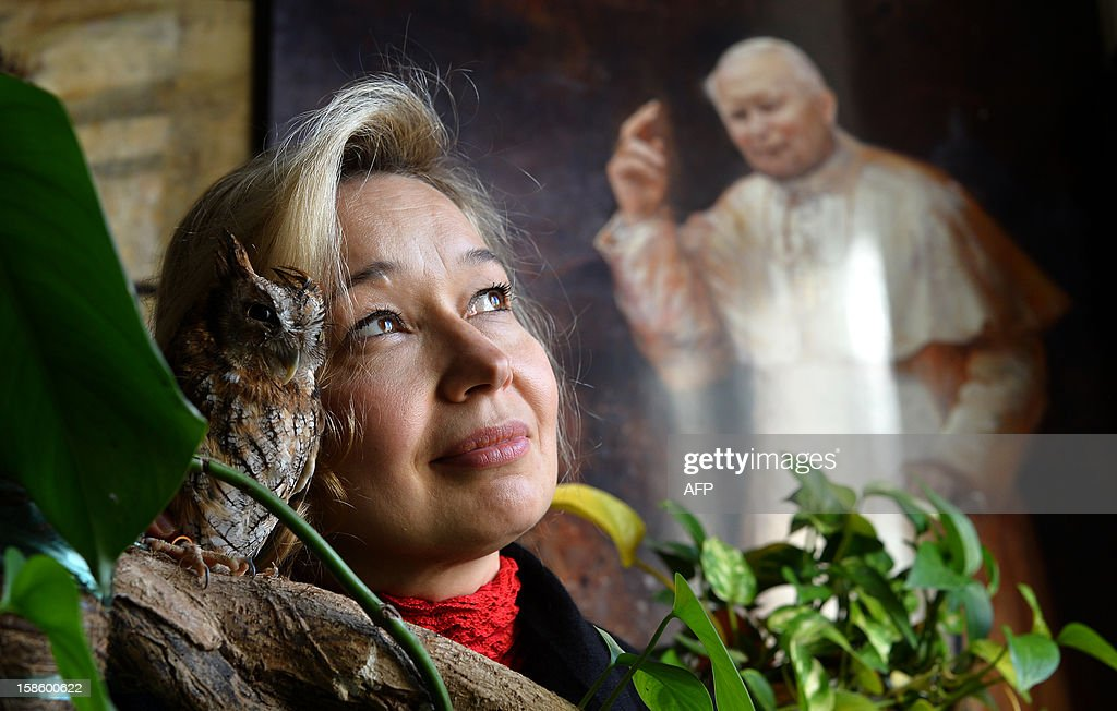 The Vatican's newest official court artist Natalia Tsarkova poses with her pet owl next to a painting of Pope John Paul II on December 18, 2012 in her studio by Rome. After Michelangelo and Raphael, the Vatican's newest official court artist is something of an unusual choice -- an ebullient Russian woman with a pet owl who meets cardinals and popes on a daily basis. AFP PHOTO / ALBERTO PIZZOLI