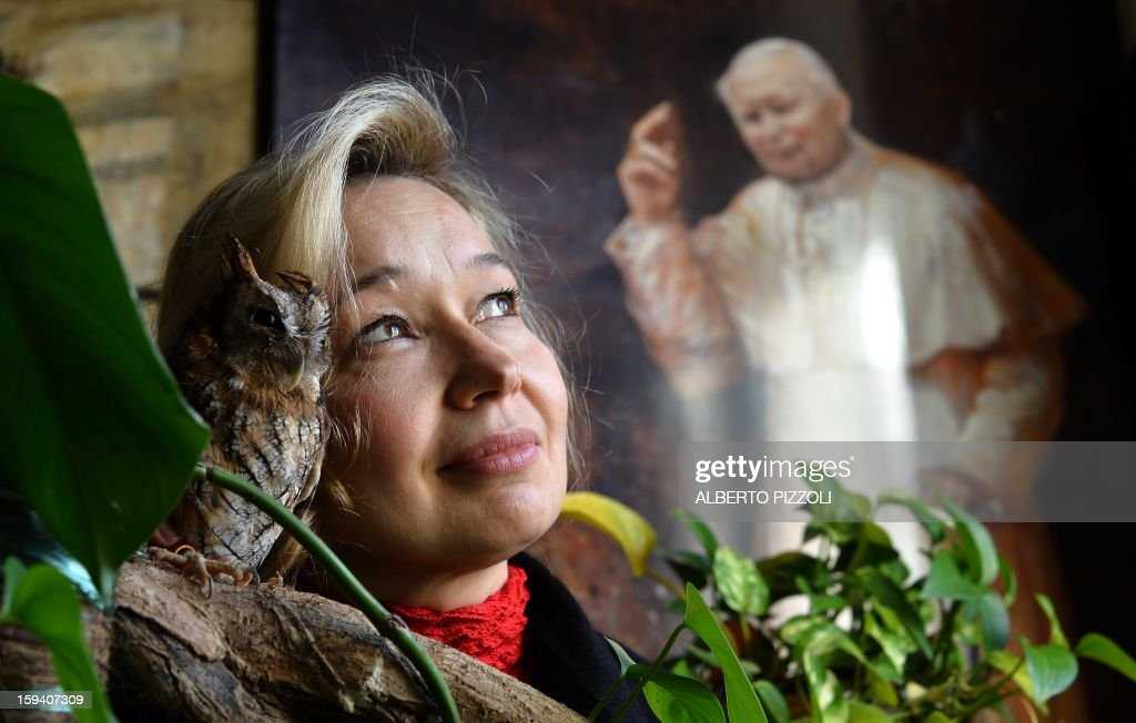 The Vatican's newest official court artist Natalia Tsarkova poses with her pet owl next to a painting of Pope John Paul II on December 18, 2012 in her studio by Rome. After Michelangelo and Raphael, the Vatican's newest official court artist is something of an unusual choice -- an ebullient Russian woman with a pet owl who meets cardinals and popes on a daily basis. AFP PHOTO / ALBERTO PIZZOLI TO GO WITH AFP STORY