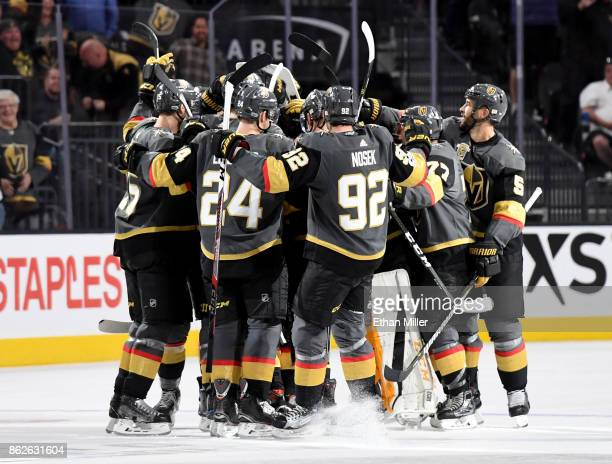 The Vegas Golden Knights celebrate on the ice after David Perron scored the gamewinning goal against the Buffalo Sabres in overtime at TMobile Arena...