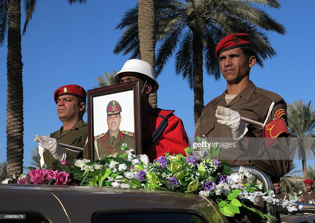 The vehicle containing the body of Mohammed al-Karoui (portrait), the commander of the army's 7th Division who was killed the previous day in a raid on an Al-Qaeda hideout in the west of the country, passes in front of the ministry of defence in Baghdad during his funeral procession on December 22, 2013. Karoui was leading an operation to attack 'hideouts of militants belonging to the Al-Qaeda organisation' in Sunni-majority Anbar province, which borders Syria. AFP PHOTO / STR