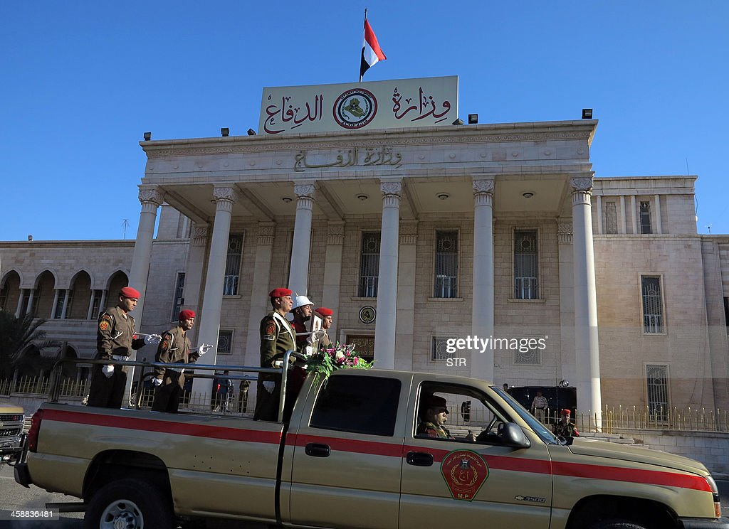 The vehicle containing the body of Mohammed al-Karoui, the commander of the army's 7th Division who was killed the previous day in a raid on an Al-Qaeda hideout in the west of the country, passes in front of the ministry of defence in Baghdad during his funeral procession on December 22, 2013. Karoui was leading an operation to attack 'hideouts of militants belonging to the Al-Qaeda organisation' in Sunni-majority Anbar province, which borders Syria. AFP PHOTO / STR