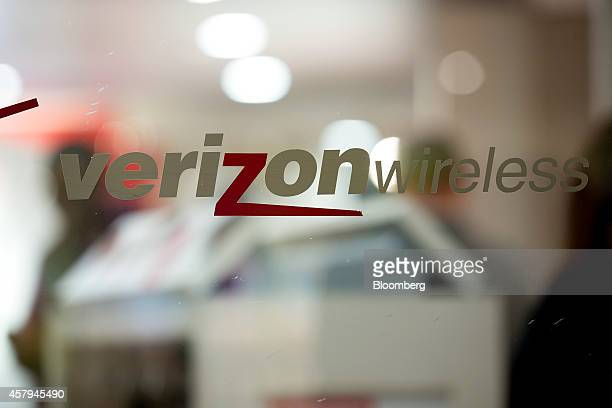 The Verizon Wireless logo hangs on a window at a retail store in Washington DC US on Thursday Oct 23 2014 Verizon Communications Inc the largest US...