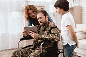 The veteran in a wheelchair came back from the army. A man in uniform in a wheelchair with his family. Man in a wheelchair shows her son and wife something on the tablet.