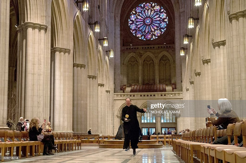 The vicar of the National Cathedral Stuart Kenworthy flips a pancake during the Shrove Tuesday Pancake Race at the National Cathedral in Washington, DC, on February 9, 2016. Shrove Tuesday, also known as Mardi Gras, precedes Ash Wednesday, the first day of Lent. / AFP / Nicholas Kamm