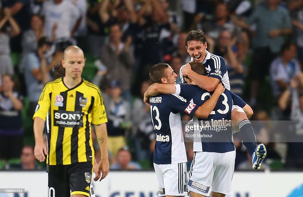 The Victory celebrate after scoring their second goal as Stein Huysegems (L) of the Phoenix looks on during the round 15 A-League match between the Melbourne Victory and Wellington Phoenix at AAMI Park on January 5, 2013 in Melbourne, Australia.