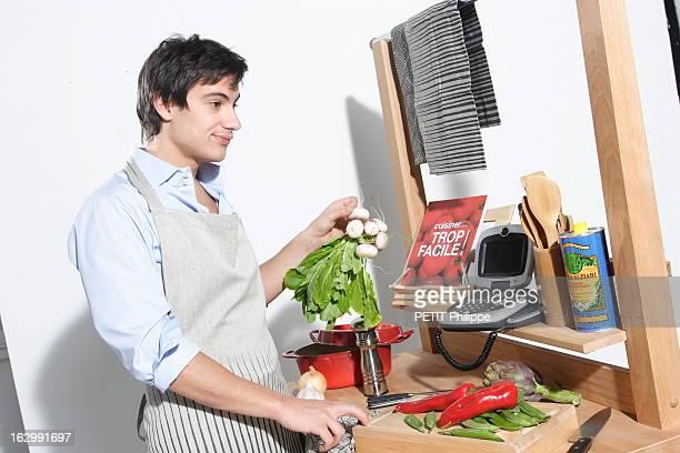 jeune homme faisant la cuisine en écoutant les explications de sa copine grâce au visiophone fixe de France Telecom chemise Agnès B comptoir de...