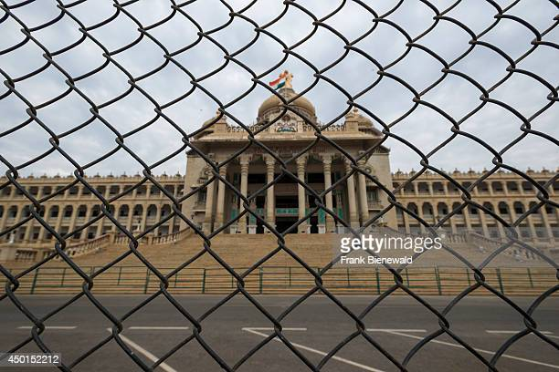 The Vidhana Soudha behind a mesh wire fence is the seat of the state legislature of Karnataka