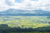 The view of Aso mountain. There is Aso mountain, rice field, town, forest and grasses in Japan.