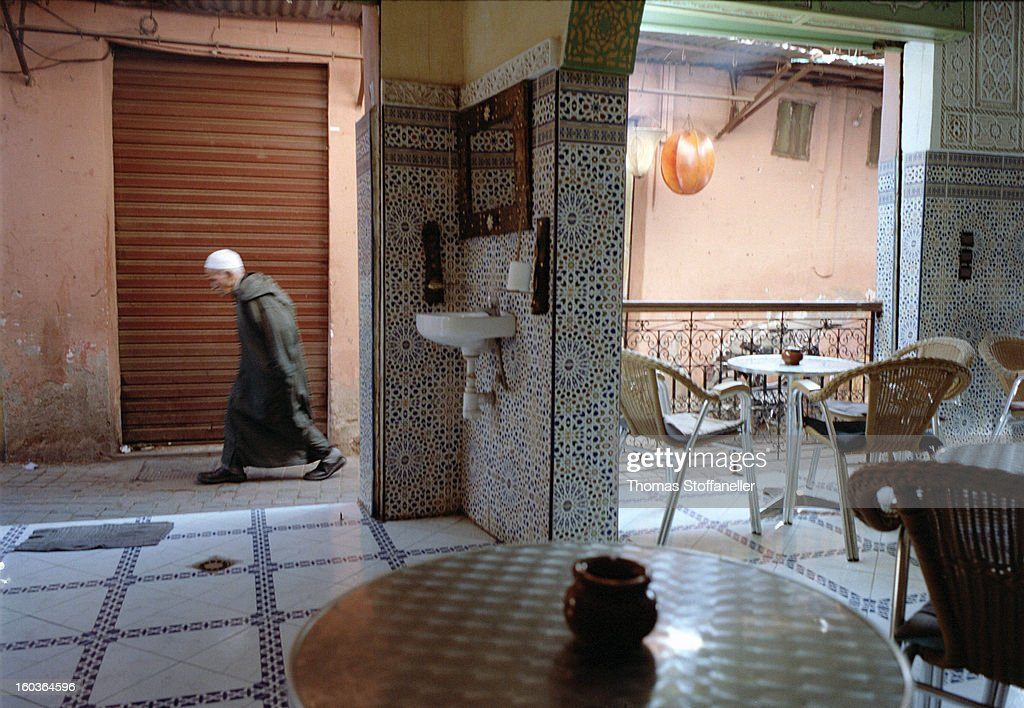CONTENT] the view out of a cafe in the streets of marrakech, morocco; a man in a traditional dress - the djellaba is walking by