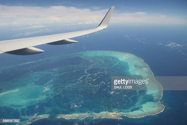 The view out the window of Air Force One with US President Barack Obama aboard over a nearby island as the airplane approaches Midway Atoll in the...