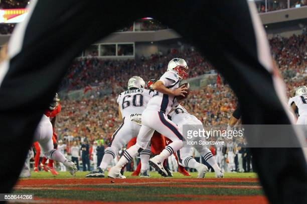 The view thru the legs of the back judge of Tom Brady of the Patriots attempting to hand the ball off during the NFL Regular game between the New...