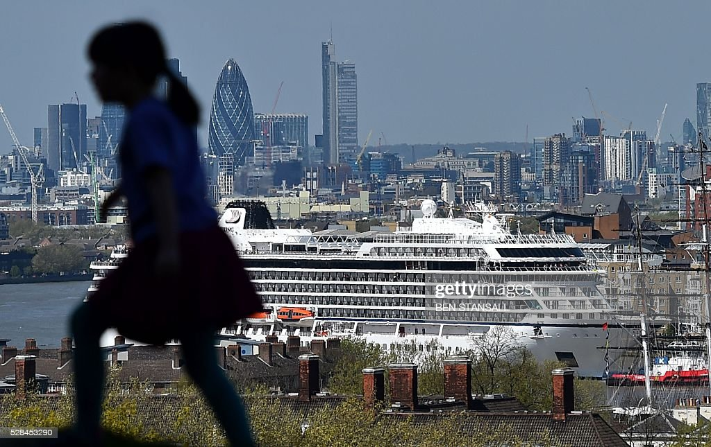 The Viking Sea cruise ship is guided by tug boats along the River Thames towards Greenwhich Pier in east London on May 5, 2016, ahead of its official naming ceremony later today. Viking Sea, the latest ocean-going crusie ship to join Viking Cruises' fleet, is set to be the largest ever cruise ship christened on the Thames. / AFP / BEN