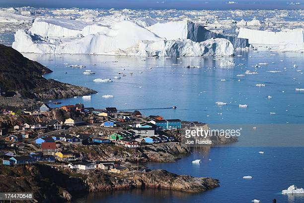 The village of Ilulissat is seen near the icebergs that broke off from the Jakobshavn Glacier on July 24 2013 in Ilulissat Greenland As the sea...