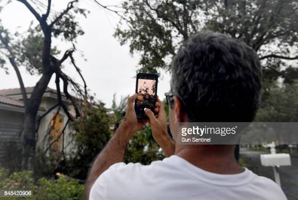 The Vineyards in Monarch Lake resident Syed Ali takes pictures of down tree limbs in his neighbor's front yard after Hurricane Irma left the Miramar...