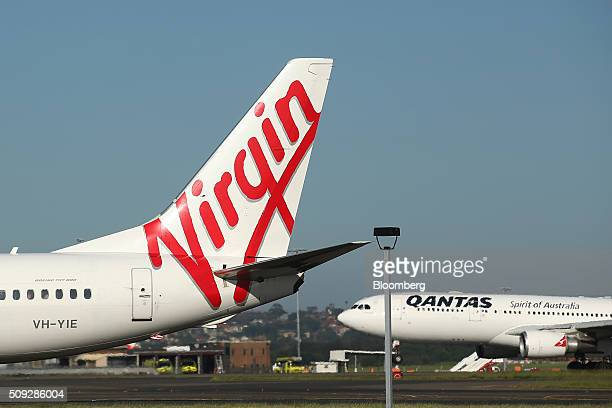 The Virgin Australia Holdings Ltd logo is displayed on the tail of a Boeing Co 737800 aircraft left as a Qantas Airways Ltd aircraft is seen right at...
