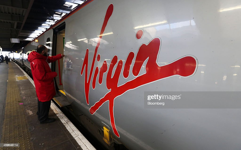 The Virgin logo sits on the side of a West Coast train, operated by Virgin Trains, as it stands beside a platform at Euston railway station in London, U.K., on Thursday, Nov. 27, 2014. Virgin Trains and partner Stagecoach Group Plc were chosen to run the London-Edinburgh rail route, fending off rival bids from FirstGroup Plc and Eurostar International Ltd. and delivering a boost for Richard Branson a month after the fatal crash involving his space venture. Photographer: Chris Ratcliffe/Bloomberg via Getty Images
