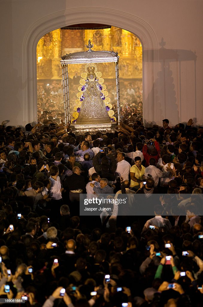 The Virgin of El Rocio is carried out the Hermitage by members of the brotherhood of Matriz de Almonte after they jumped the fence, el salto de la reja, in the early hours of May 20, 2013 in Sanlucar De Barrameda, Spain. The Romeria del Rocio procession brings together roughly a million pilgrims each year making their way for as long as seven days from throughout Andalusia by foot, on horsebacks and horse drawn carriages, to the doors of the Hermitage of El Rocio. On Sunday night, after reciting the Holy Rosary at candlelight, and the passing of all the simpecados in front of the chapel, with the one from the brotherhood of Matriz de Almonte as the last one, el salto de la reja begins, the jumping of the fence surrounding the Hermitage after which the Virgin of El Rocio is carried out onto the sandy streets of the small town for the 'Blanca Paloma' procession. Then, the long camino home begins. Dating back from 1653, it was in 1758, when the Virgin of Las Rocinas became known as the Virgin of El Rocio, that the pilgrimage started to take place in the weekend of the Sunday of Pentecost, 50 days after Easter Sunday.