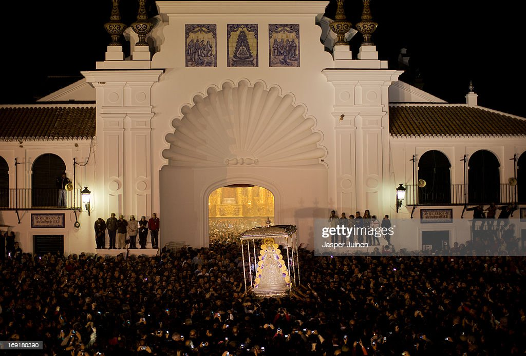 The Virgin of El Rocio is carried out the Hermitage by members of the brotherhood of Matriz de Almonte after they jumped the fence, el salto de la reja, in the early hours of May 20, 2013 in El Rocio, Spain. The Romeria del Rocio procession brings together roughly a million pilgrims each year making their way for as long as seven days from throughout Andalusia by foot, on horsebacks and horse drawn carriages, to the doors of the Hermitage of El Rocio. On Sunday night, after reciting the Holy Rosary at candlelight, and the passing of all the simpecados in front of the chapel, with the one from the brotherhood of Matriz de Almonte as the last one, el salto de la reja begins, the jumping of the fence surrounding the Hermitage after which the Virgin of El Rocio is carried out onto the sandy streets of the small town for the 'Blanca Paloma' procession. Then, the long camino home begins. Dating back from 1653, it was in 1758, when the Virgin of Las Rocinas became known as the Virgin of El Rocio, that the pilgrimage started to take place in the weekend of the Sunday of Pentecost, 50 days after Easter Sunday.