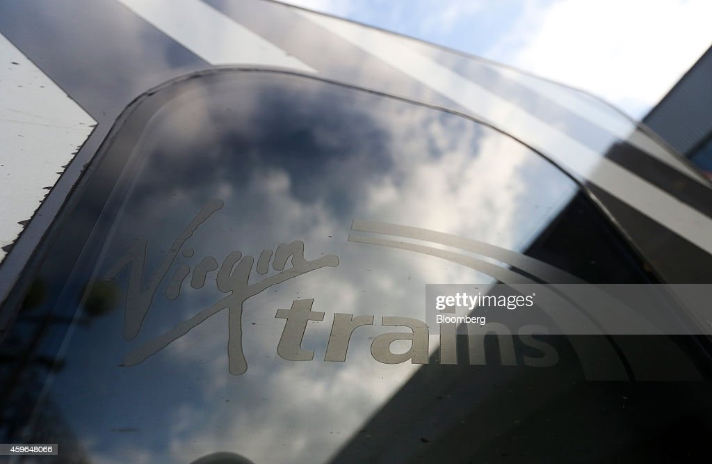 The Virgin Trains logo sits on a window of a West Coast train as it stands beside a platform at Euston railway station in London, U.K., on Thursday, Nov. 27, 2014. Virgin Trains and partner Stagecoach Group Plc were chosen to run the London-Edinburgh rail route, fending off rival bids from FirstGroup Plc and Eurostar International Ltd. and delivering a boost for Richard Branson a month after the fatal crash involving his space venture. Photographer: Chris Ratcliffe/Bloomberg via Getty Images