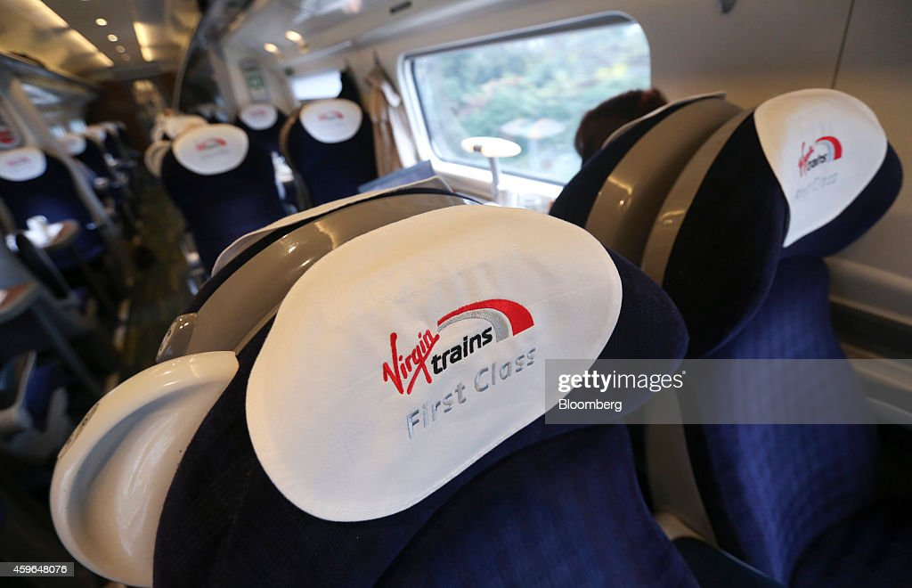 The Virgin Trains logo sits on first class carriage seat antimacassars on board a West Coast train as it travels from London to Milton Keynes, U.K., on Thursday, Nov. 27, 2014. Virgin Trains and partner Stagecoach Group Plc were chosen to run the London-Edinburgh rail route, fending off rival bids from FirstGroup Plc and Eurostar International Ltd. and delivering a boost for Richard Branson a month after the fatal crash involving his space venture. Photographer: Chris Ratcliffe/Bloomberg via Getty Images