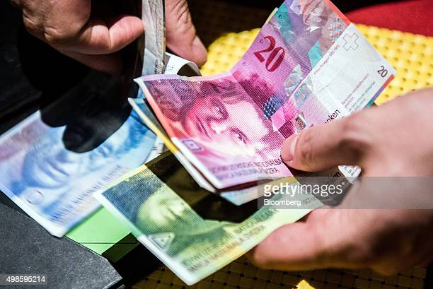 The visage of Arthur Honegger a Swiss composer sits on a 20 Swiss franc banknote as waiter counts payment at a cafe in Lugano Switzerland on Friday...