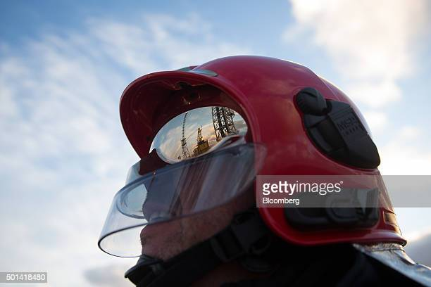 The visor of a firefighter's helmet reflects a gas burn off venting pipe as he stands on the helicopter deck of the Armada gas condensate platform...