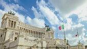 memorial monument the Vittoriano or Altar of the Fatherland, in Venezia square, with waving italian flag. Italian and Rome patriotic symbols, located on the Campidoglio hill in Rome