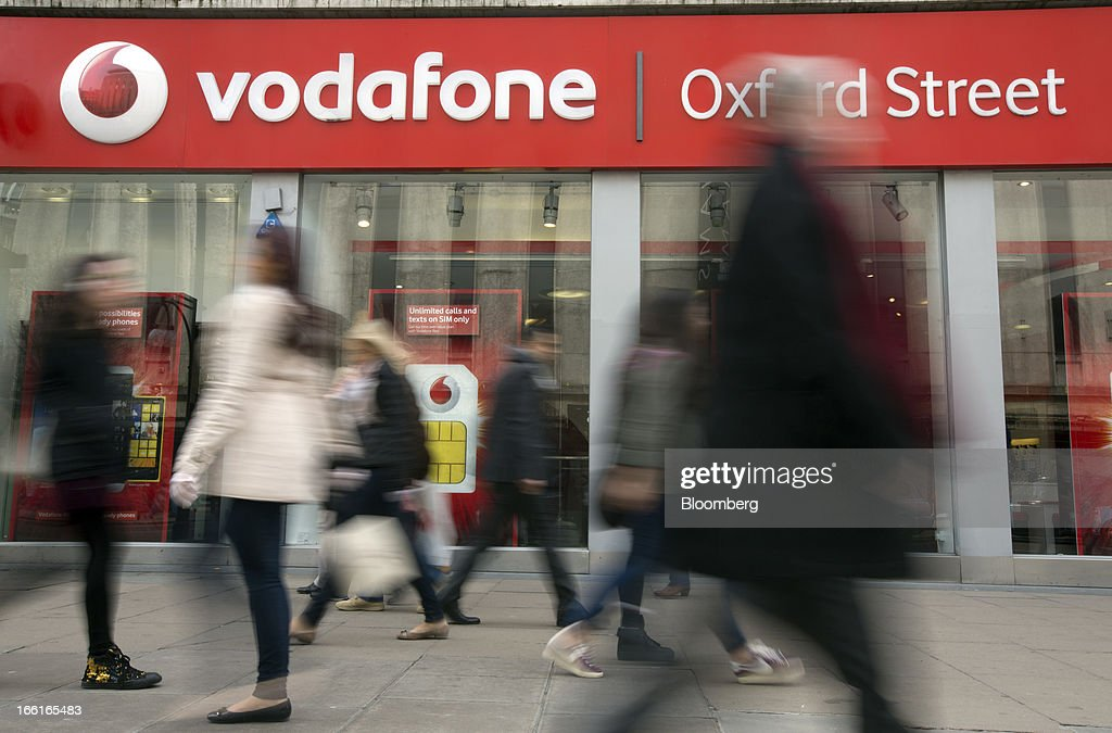 The Vodafone Group Plc logo sits above the windows of the company's store on Oxford Street in London, U.K., on Monday, April 8, 2013. Vodafone Group Plc is restating its results going back two fiscal years as new international accounting rules for joint ventures cut historical revenue and earnings. Photographer: Simon Dawson/Bloomberg via Getty Images