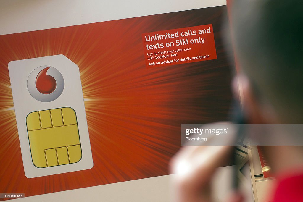 The Vodafone Group Plc logo sits on a poster of a giant SIM card displayed inside the company's Oxford Street store in London, U.K., on Monday, April 8, 2013. Vodafone Group Plc is restating its results going back two fiscal years as new international accounting rules for joint ventures cut historical revenue and earnings. Photographer: Simon Dawson/Bloomberg via Getty Images
