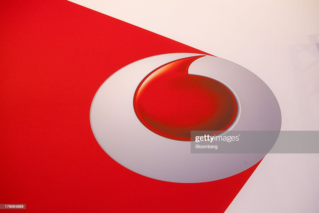 The Vodafone Group Plc logo sits on display on the eve of the opening of the IFA consumer electronics show in Berlin, Germany, on Thursday, Sept. 5, 2013. Samsung showed the Galaxy Gear yesterday at IFA, Europe's largest consumer-electronics show, as it races Apple and Sony Corp. to carve a share of the market for wearable technology amid slowing growth in smartphones. Photographer: Krisztian Bocsi/Bloomberg via Getty Images