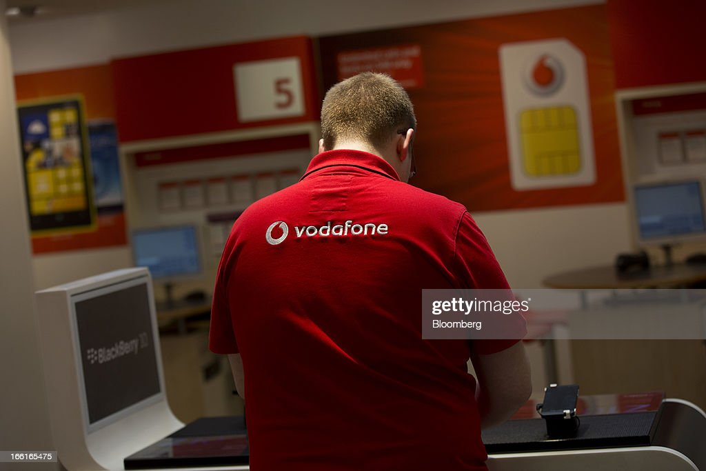 The Vodafone Group Plc logo sits on the back of an employee's shirt as he works inside the company's Oxford Street store in London, U.K., on Monday, April 8, 2013. Vodafone Group Plc is restating its results going back two fiscal years as new international accounting rules for joint ventures cut historical revenue and earnings. Photographer: Simon Dawson/Bloomberg via Getty Images
