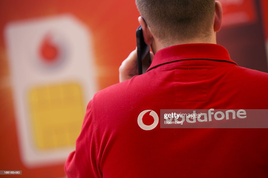 The Vodafone Group Plc logo sits on the back of an employee's shirt as speaks on a mobile handset inside the company's Oxford Street store in London, U.K., on Monday, April 8, 2013. Vodafone Group Plc is restating its results going back two fiscal years as new international accounting rules for joint ventures cut historical revenue and earnings. Photographer: Simon Dawson/Bloomberg via Getty Images