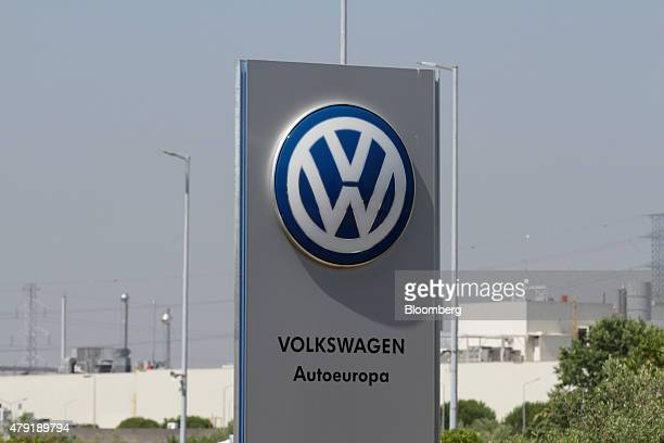The Volkswagen AG logo sits on a sign outside the VW Autoeuropa automobile manufacturing plant in Palmela Portugal on Tuesday June 30 2015 Car...