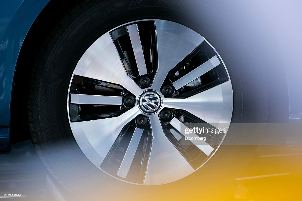 The Volkswagen badge (VW) sits the wheel hub of a VW e-Golf electric automobile, produced by Volkswagen AG (VW), as it stands inside one of the automaker's glass delivery towers at the VW factory in Wolfsburg, Germany, on Friday, April 29, 2016. Porsche Automobil Holding SE, the investment vehicle of the billionaire family that controls VW, stuck to a goal of making acquisitions beyond the beleaguered carmaker, even as its dwindling cash on hand reduces the scope of possible transactions. Photographer: Krisztian Bocsi/Bloomberg via Getty Images