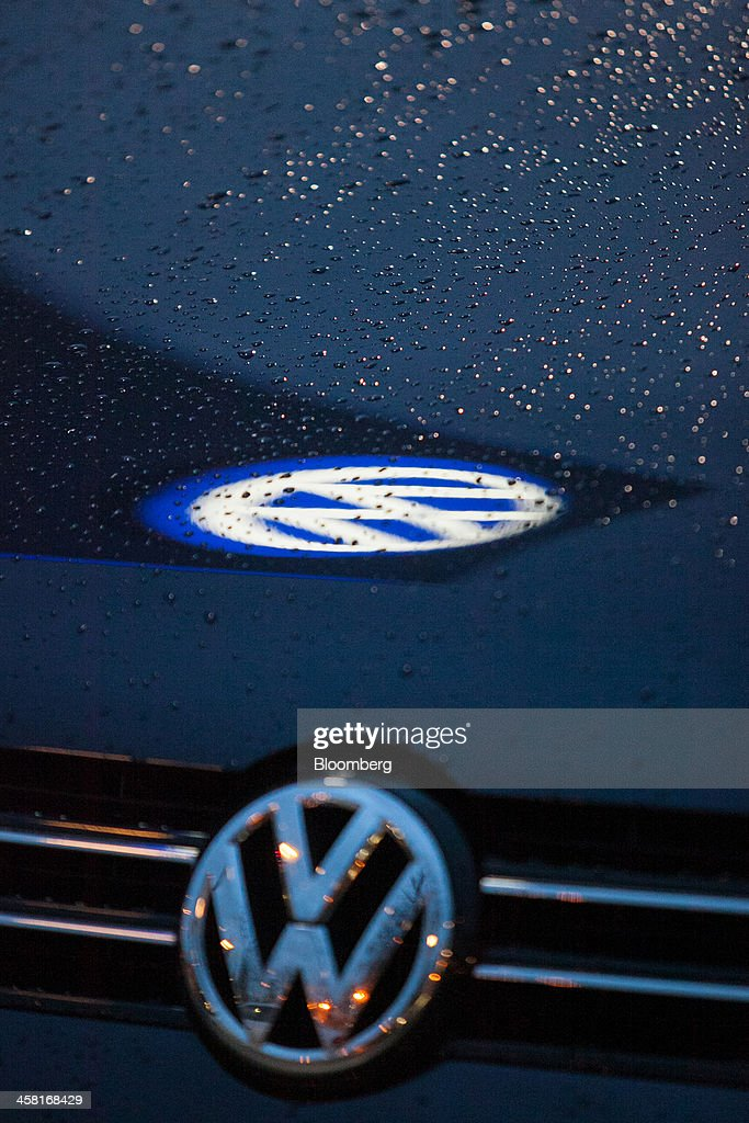 The VW badge sits on the hood of a Volkswagen AG Touran outside an automobile showroom in Berlin, Germany, on Thursday, Dec. 19, 2013. European new-car sales rose a third consecutive month in November, the longest period of gains in four years. Photographer: Krisztian Bocsi/Bloomberg via Getty Images
