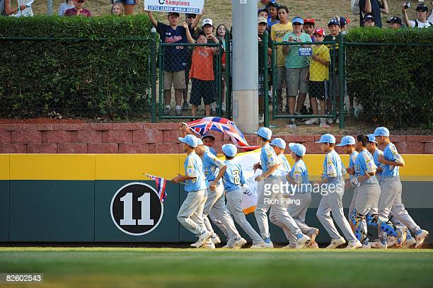 The Waipio Little League team runs with the state flag of Hawaii after winning the World Series Championship game against the Matamoros Little League...