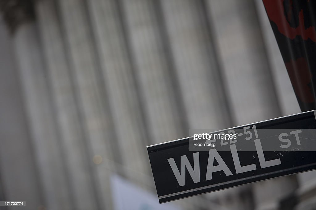 The Wall St. sign is posted near the New York Stock Exchange (NYSE) in New York, U.S., on Friday, June 28, 2013. U.S. stocks fell, after the biggest three-day rally since January for the Standard & Poor's 500 Index, before data on consumer sentiment and business activity as investors weighed statements from Federal Reserve officials. Photographer: Scott Eells/Bloomberg via Getty Images
