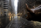 The Wall Street bronze Bull looks out to an empty Broadway in Lower Manhattan New York early August 28 2011 as Hurricane Irene hits the city and Tri...