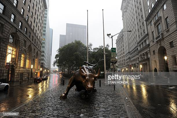 The Wall Street bronze Bull sits between empty streets in Lower Manhattan New York early August 28 2011 as Hurricane Irene hits the city and Tri...