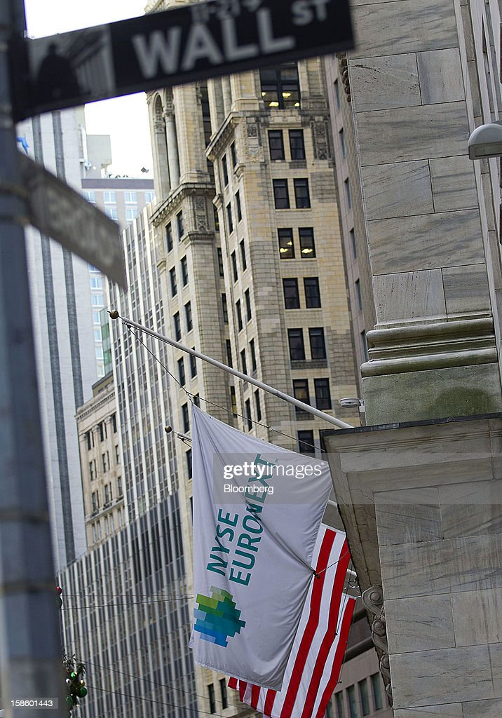 The Wall Street sign is seen as a NYSE Euronext and U.S. flag flies outside of the New York Stock Exchange (NYSE) in New York, U.S., on Thursday, Dec. 20, 2012. InterContinentalExchange Inc. (ICE), the 12-year-old energy and commodity futures bourse, agreed to acquire NYSE Euronext for cash and stock worth $8.2 billion, moving to take control of the world's biggest equities market. Photographer: Jin Lee/Bloomberg via Getty Images