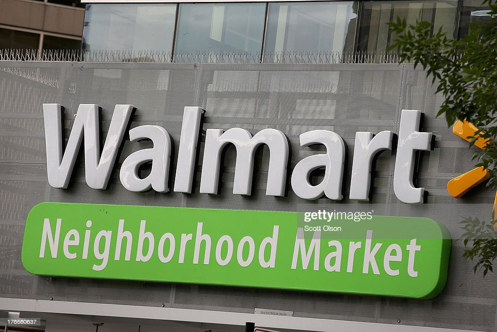 The Walmart logo is displayed aove a Walmart Neighborhood Market store on August 15, 2013 in Chicago, Illinois. Walmart, the world's largest retailer, reported a surprise decline in second-quarter same-store sales today. The retailer also cut its revenue and profit forecasts for the fiscal year.