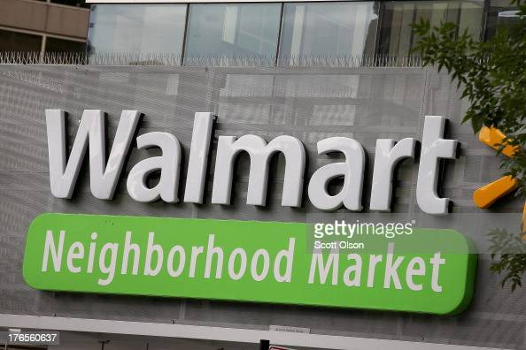 The Walmart logo is displayed aove a Walmart Neighborhood Market store on August 15 2013 in Chicago Illinois Walmart the world's largest retailer...
