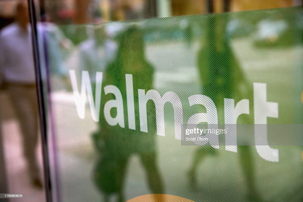 The Walmart logo is displayed in the window of a Walmart Neighborhood Market store on August 15, 2013 in Chicago, Illinois. Walmart, the world's largest retailer, reported a surprise decline in second-quarter same-store sales today. The retailer also cut its revenue and profit forecasts for the fiscal year.