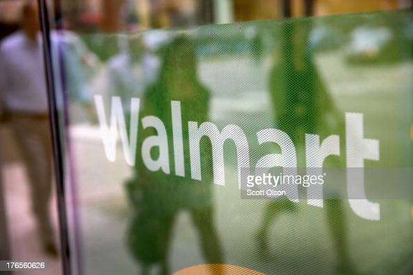 The Walmart logo is displayed in the window of a Walmart Neighborhood Market store on August 15 2013 in Chicago Illinois Walmart the world's largest...