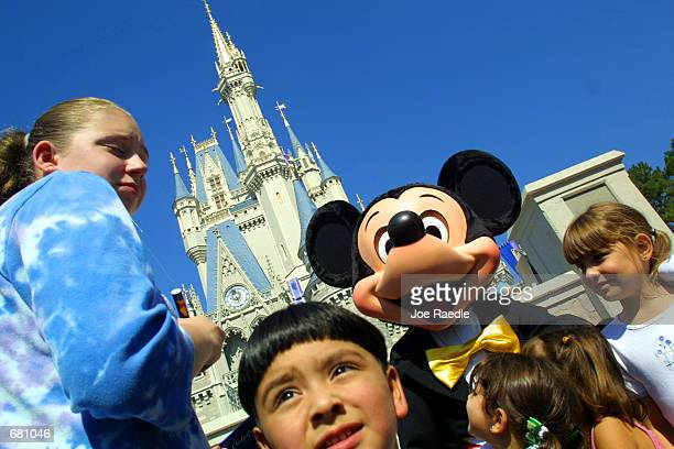 The Walt Disney character Mickey Mouse greets children in front of Cinderella's Castle at Magic Kingdom November 11 2001 in Orlando Florida