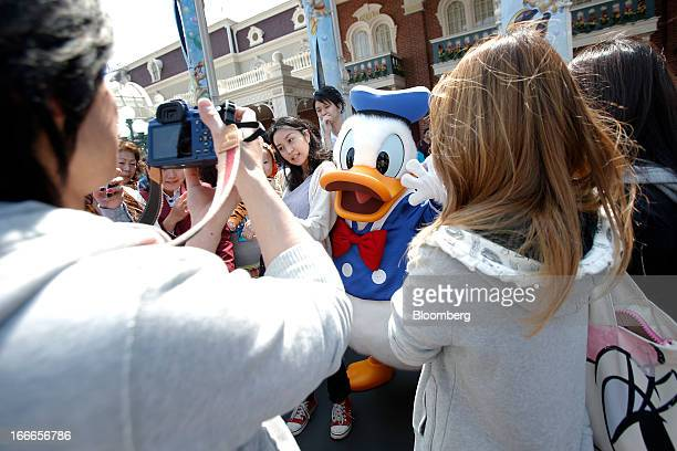 The Walt Disney Co character Donald Duck poses for a photograph with visitors at Tokyo Disneyland operated by Oriental Land Co in Urayasu City Chiba...